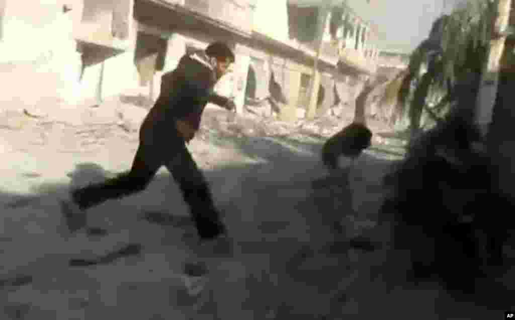 This image taken from video obtained from Shaam News Network shows men running during heavy bombing from military warplanes in Houla, Syria, November 6, 2012.