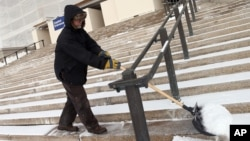 Paul Linquist braves subzero temperatures to shovel snow from the steps of the Minnesota State Capitol in St. Paul in preparation for the start of the 2015 legislative session, Jan. 6, 2015.