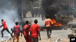 Para pengunjuk rasa yang membakar barikade di jalanan bentrok dengan pasukan keamanan di Conakry, Guinea (18/4). Pasukan keamanan membubarkan pengunjuk rasa dengan gas air mata dan menangkap dua pemimpin oposisi.