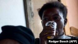 Une femme boit une bière dans un bar illégal à 15 km du de Cape Town le 10 février 2012.