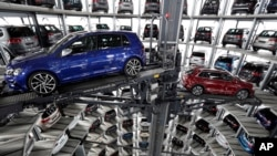 FILE - Volkswagen cars are lifted inside a delivery tower of the company in Wolfsburg, Germany, March 14, 2017. Due to rising demand for German products, the U.S. trade deficit with Germany has nearly doubled in the past 10 years from some 28.8 billion euros in 2006 to 49 billion euros in 2016, according to German data.