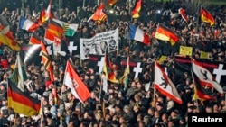 FILE - Supporters of anti-immigration movement Patriotic Europeans Against the Islamization of the West (PEGIDA) hold flags during demonstration in Dresden, Germany, Jan. 12, 2015.