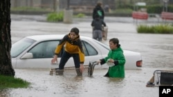 Aidan Perez, left, 12, and Christopher Dow, 11, use a shopping cart to get around after a severe storm flooded a shopping center parking lot in Healdsburg, Calif., Dec. 11, 2014.