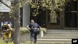 Một viên cảnh sát tiến gần đến lối ra vào của Đại học Oilkos, ở Oakland
