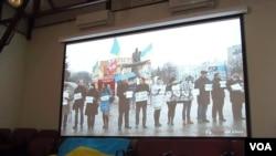2014年在莫斯科的一场研讨会上,乌克兰活动人士展示国旗和乌克兰反政府示威活动视频。