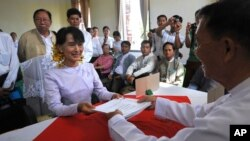 Burma's opposition leader Aung San Suu Kyi presents expenses, that she used during her political campaign in recent by-elections, at the Thanlyin township election commission office, on the outskirts of Rangoon.