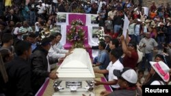 Friends and supporters gather next to the coffin of slain environmental rights activist Berta Caceres as they attend a Mass outside the Virgen de Lourdes church in the town of La Esperanza, outside Tegucigalpa, Honduras, March 5, 2016.