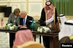 Saudi Arabia's King Salman bin Abdulaziz Al Saud (right) and U.S. President Donald Trump sign a joint security agreement at the Royal Court in Riyadh, Saudi Arabia, May 20, 2017.