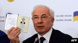 Ukraine's former prime minister, Mykola Azarov, displays his Ukrainian internal passport at a press conference in Moscow, August 3, 2015