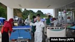 Korban luka-luka akibat gempa 6,2 magnitudo yang mengguncang pada 15 Januari lalu sedang dirawat di luar sebuah rumah sakit karena takut gempa susulan, di Mamuju, Sulawesi Barat, Minggu, 17 Januari 2021. (Foto: Adek Berry/AFP)