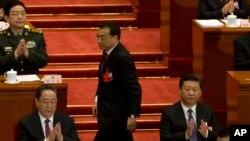 在全国人大开幕式上,中国总理李克强(中)从国家主席习近平(右)身后走上台做报告。(2016年3月5日)