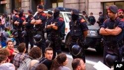 Polisi Catalonia, Catalan Mossos d'Esquadra, melindungi kendaraan yang yang mengangkut petugas pengawal warga sipil saat berlangsungnya aksi unjuk rasa di Barcelona, Spanyol, 20 September 2017. (Foto: dok).
