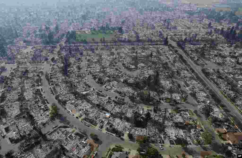 Homes burned by a wildfire are seen in Santa Rosa, California, Oct. 11, 2017. Wildfires whipped by powerful winds swept through Northern California sending residents on a headlong flight to safety through smoke and flames as homes burned.