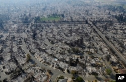 FILE - Homes burned by a wildfire are seen, Oct. 11, 2017, in Santa Rosa, Calif.