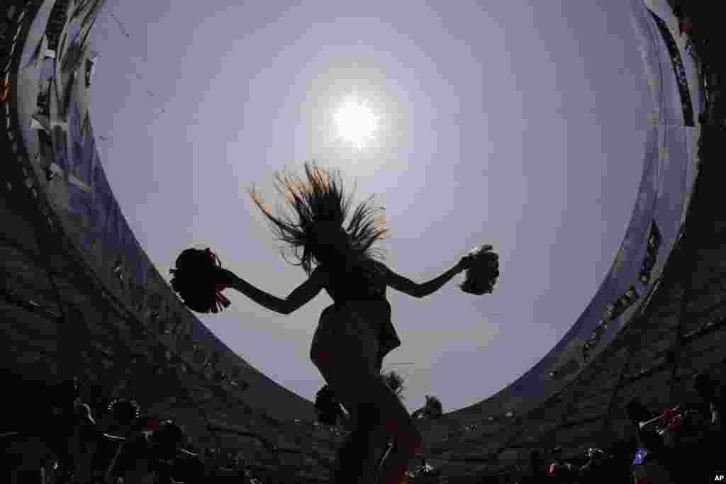 Cheerleaders are silhouetted as they rehearse on the track at the Bird's Nest Stadium in preparation for the upcoming World Athletics Championships in Beijing, China.