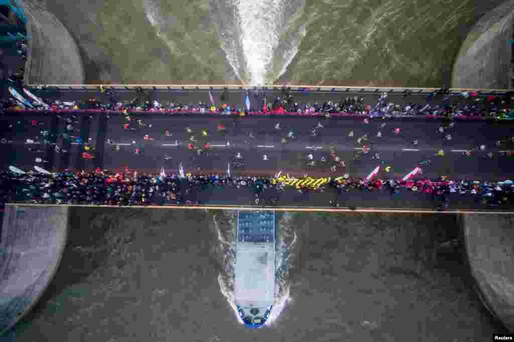 دوندگان ماراتن لندن از روی پل برج مشهور این شهر عبور می کنند.