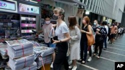 People queue up for last issue of Apple Daily at a newspaper booth at a downtown street in Hong Kong, Thursday, June 24, 2021. (AP)