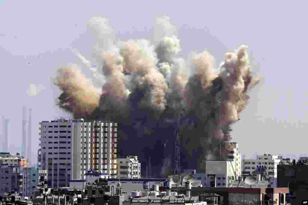 Smoke, dust and debris rise after an Israeli strike, Gaza City , Friday, Aug. 8, 2014