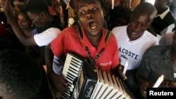 A man plays an accordion during a prayer session following an attack by gunmen at the Garissa University College campus, along the streets of the capital Nairobi, April 7, 2015. The Kenyan air force has destroyed two al Shabaab camps in Somalia, it said o