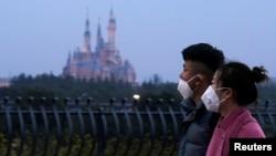 戴着口罩的上海市民从春节期间关闭的迪斯尼乐园旁走过。(2020年1月24日)