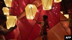 Một bé gái đứng bên những chiếc lồng đèn trong lễ hội Trung Thu tại Công viên Victoria ở Hong Kong.