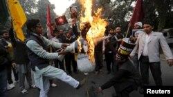 4일 인도 뉴델리의 사우디 대사관 앞에 집결한 시아파 교도들이 사우디 정부의 시아파 성직자 처형에 항의하며 살만 빈 압둘라지즈 사우디 국왕의 모형을 불에 태우고 있다.