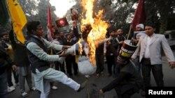 Shi'ite Muslims burn a representation of Saudi King Salman bin Abdulaziz during a protest against the execution in Saudi Arabia of cleric Nimr al-Nimr, in front of Saudi Arabia's embassy in New Delhi, India, Jan. 4, 2016.
