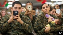 A group of Marines look on, ready to snap pictures, as President Barack Obama thanks service members and their families at Marine Corps Base Hawaii in Kaneohe Bay, Dec. 25, 2015.
