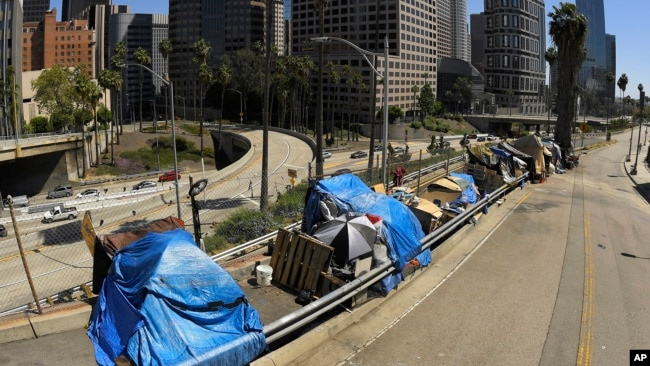 FILE - This May 21, 2020, file photo shows a homeless encampment on Beaudry Avenue as traffic moves along Interstate 110 in downtown Los Angeles. Over three days and nights this week, census takers are going to shelters, soup kitchens, mobile food van sto