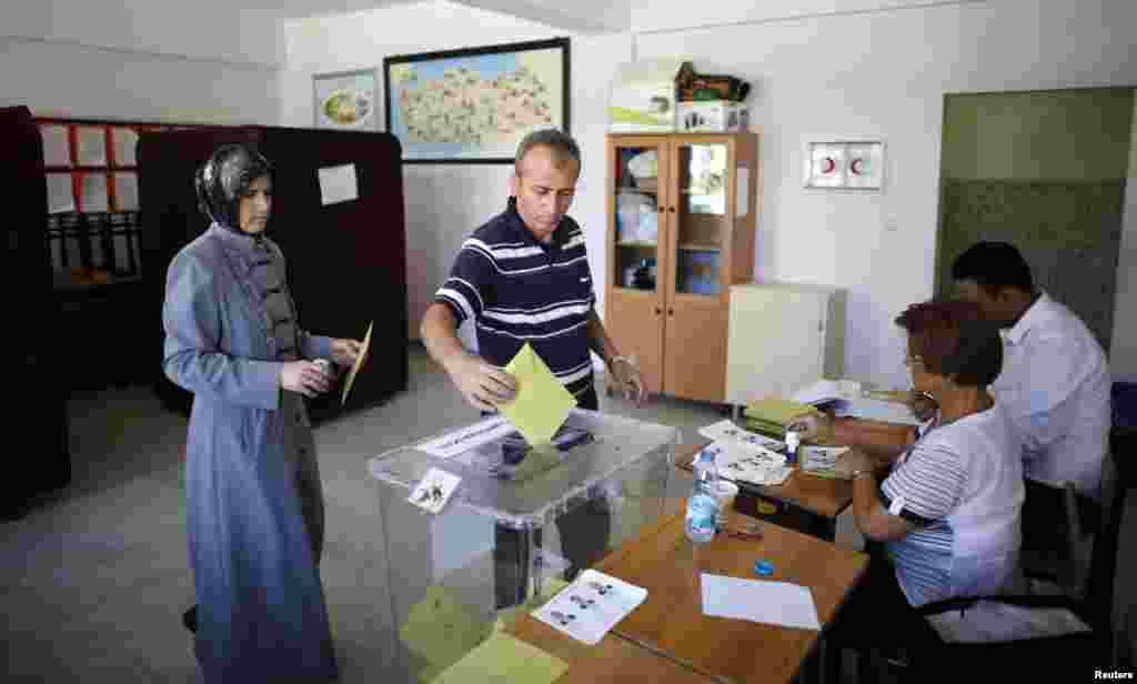 اتوار کی صبح ایک پولنگ اسٹیشن میں لوگ ووٹ ڈال رہے ہیں۔