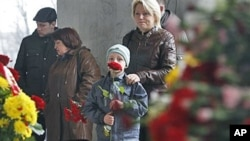 People react as they stand at an entrance to the Oktyabrskaya subway station in Minsk, Belarus, April 13, 2011