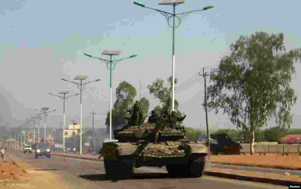 A tank patrols one of the main roads in the South Sudanese capital Juba, Dec. 16, 2013. The South Sudanese president declared a curfew in the capital Juba on Monday after clashes overnight between rival factions of soldiers.
