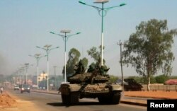 A military tank patrols along one of the main roads in the South Sudanese capital Juba, Dec. 16, 2013. The South Sudanese president declared a curfew in the capital Juba on Monday after clashes overnight between rival factions of soldiers.