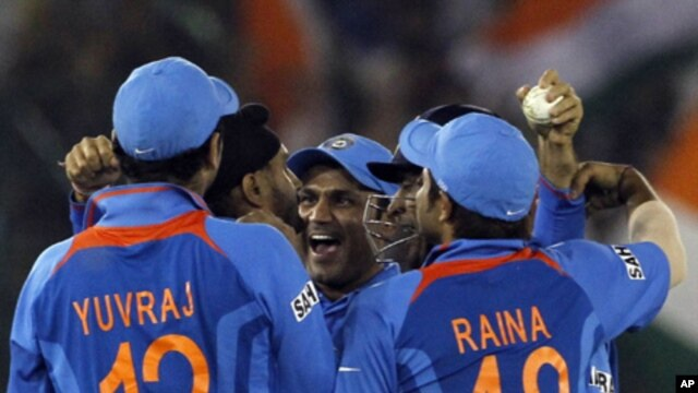 India's Harbhajan Singh (2nd L) is congratulated by teammates Yuvraj Singh (L), Virender Sehwag (C), captain and wicketkeeper Mahendra Singh Dhoni and Suresh Raina (R) after taking the wicket of Pakistan's captain Shahid Afridi during their ICC Cricket Wo