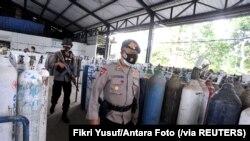 Para polisi menjaga distribusi oksigen di tempat isi ulang di tengah lonjakan kasus COVID-19 di Mengwi, Badung, Bali, 22 Juli 2021. (Foto: Fikri Yusuf/Antara Foto via Reuters