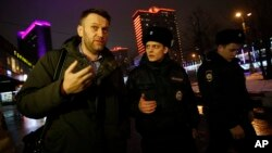 Russian opposition activist Alexei Navalny, left, is briefly detained by police officers after defying his house arrest to speak on Radio Ekho Moskvy in Moscow, Jan. 14, 2015.