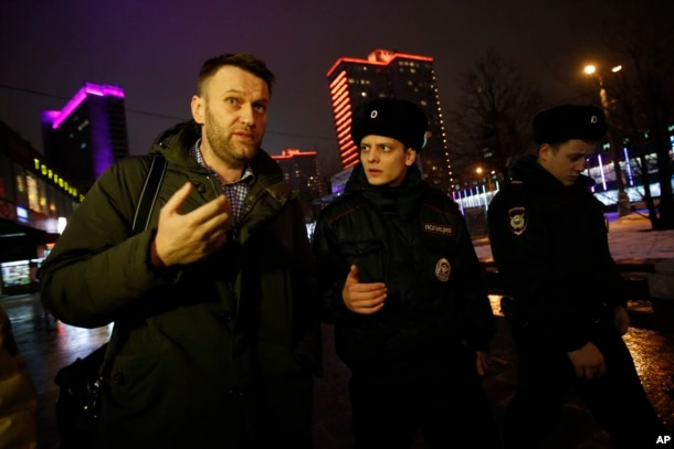 FILE - Russian opposition activist Alexei Navalny, left, is briefly detained by police after defying his house arrest to speak on Radio Ekho Moskvy in Moscow, Jan. 14, 2015.