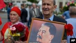 រូបឯកសារ៖ ក្រុមអ្នកគាំទ្របក្សកុម្មុយនិស្តរុស្ស៊ី កាន់រូបថតលោក Josef Stalin មេដឹកនាំសូវៀត ដើម្បីរំឭកខួបទី៧១នៃជ័យជម្នះលើប្រទេសជប៉ុនក្នុងសង្គ្រាមលោកលើកទី២ នៅទីក្រុងមូស្គូ ប្រទេសរុស្ស៊ី កាលពីខែ កញ្ញា ឆ្នាំ២០១៧។