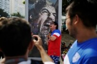Fans take pictures with a Luis Suarez poster in Rio.