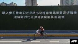 一名戴著口罩的婦女從武漢街頭一幅宣傳習近平湖北講話的大標語前騎車而過。 (2020年3月10日)