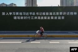 Một phụ nữ mang khẩu trang đi ngang qua một bảng quảng cáo tuyên truyền về Chủ tịch Tập Cận Bình ở Vũ Hán (AFP)