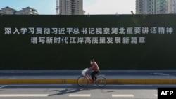 一名戴着口罩的妇女从武汉街头一幅宣传习近平湖北讲话的大标语前骑车而过。(2020年3月18日)