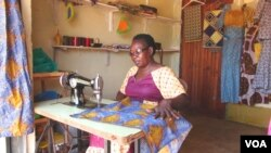 Isidoro Magda makes a dress in her shop at the Kampala suburb of Kisugu, Uganda. Magda says learning how to sew and setting up her own business put her on her way to financial independence. (Simon Peter Apiku/VOA)