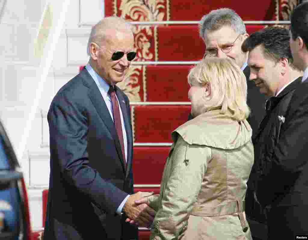 U.S. Vice President Joe Biden (left) shakes hands with Ukrainian and U.S. officials upon his arrival at Boryspil International airport outside Kyiv, Ukraine, April 21, 2014.