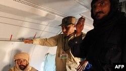 Sayful Islom Qaddafiy samolyotda Zintanga ko'chirilmoqda, Liviya, 19-noyabr, 2011-yil