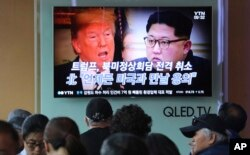 People watch a TV screen showing images of U.S. President Donald Trump, left, and North Korean leader Kim Jong Un during a news program at the Seoul Railway Station in Seoul, South Korea, May 25, 2018.