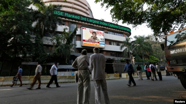 People watch a large screen displaying India's benchmark share index on the facade of the Bombay Stock Exchange (BSE) building in Mumbai, Dec. 9, 2013