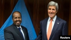 U.S. Secretary of State John Kerry (R) and Somalia's President Hassan Sheikh Mohamud shake hands before a meeting at Addis Ababa Bole International Airport, May 3, 2014.