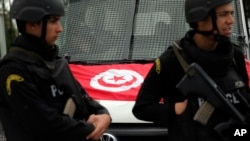 FILE - A Tunisian national flag is seen on a police vehicle as policemen stand guard following an attack by gunmen, claimed later by Islamic State, in Tunis, Tunisia, March 20, 2015.
