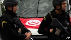 Le drapeau tunisien sur le capot d'un véhicule derrière des policiers qui montent la garde sur le lieu d'une fusillade, Tunis, Tunisie, 20 mars 2015. (AP Photo/Christophe Ena)
